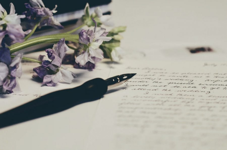A pen and a flower atop a piece of paper are pictured.