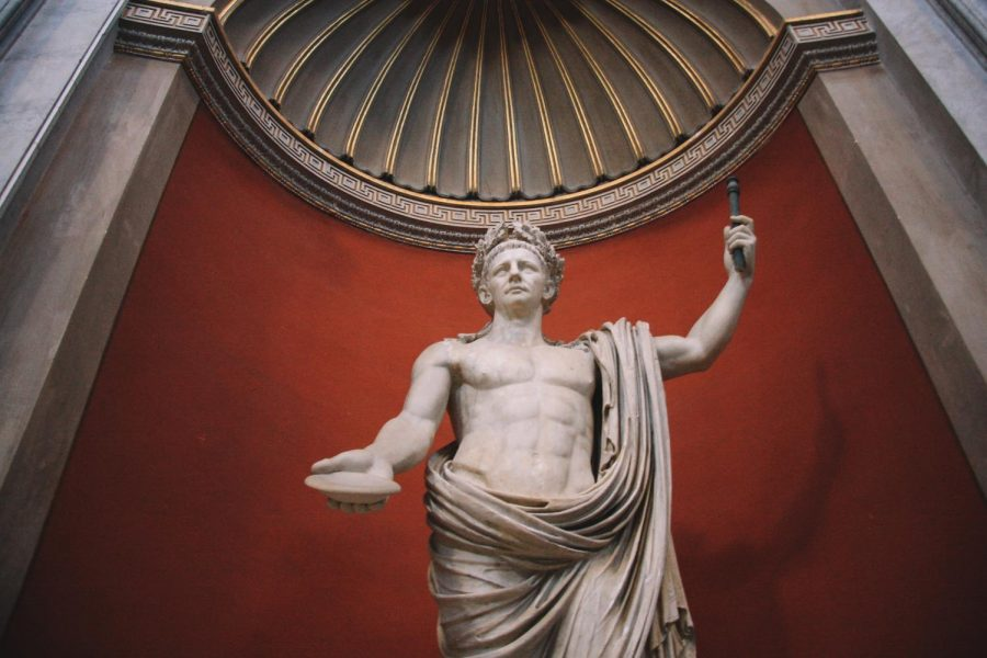 A statue of Julius Caesar stands, hands outstretched, on a red background.