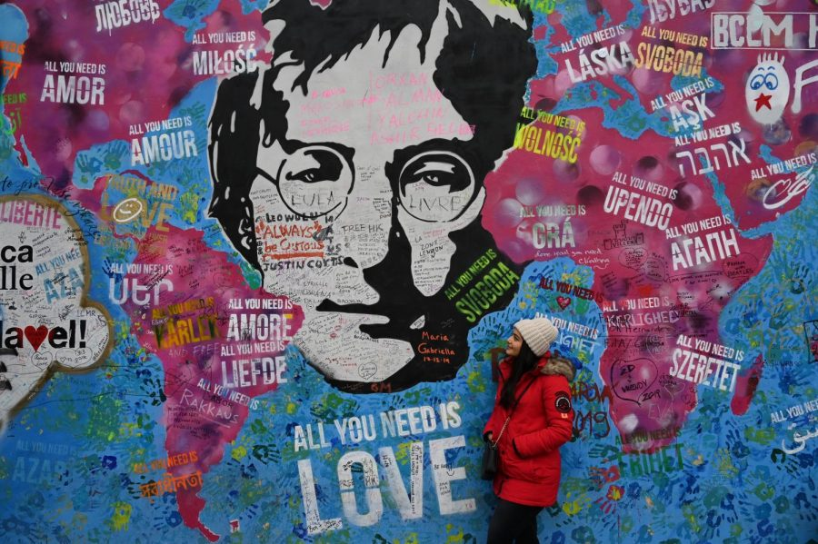 A woman looks up at a tribute mural to John Lennon.